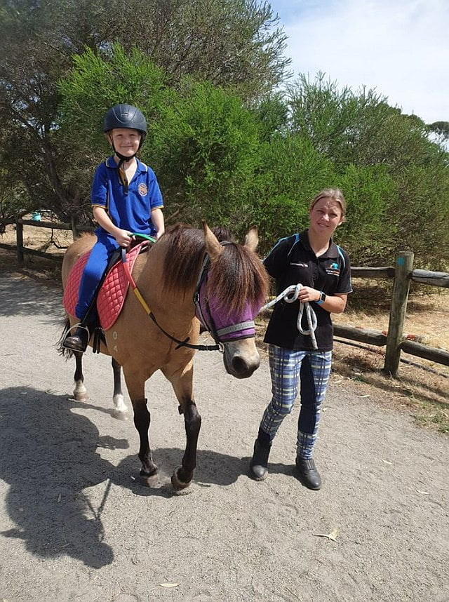 PVRC - a young lady assists a young girl on a horse