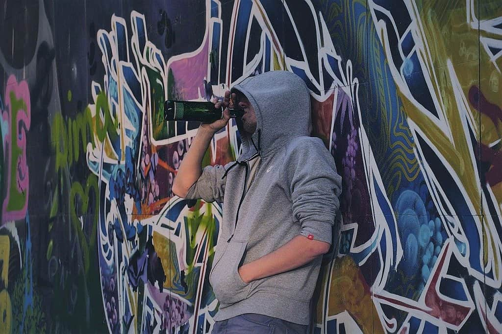 young man drinking from a bottle in front of wall with graffiti